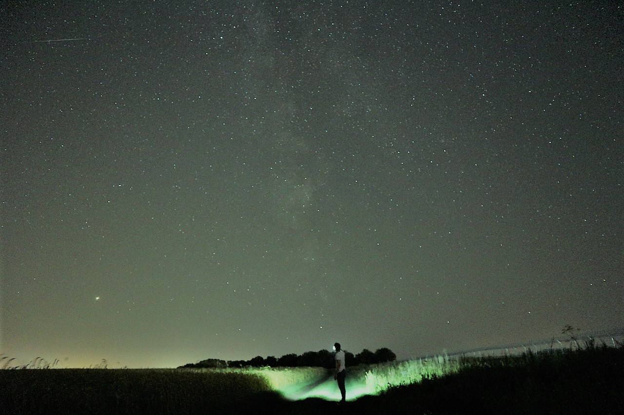 человек с фонариком на фоне звезд